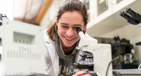 student smiling in the biology labs
