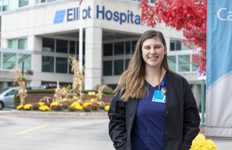 student stands outside Elliot Hospital where she works as an LNA