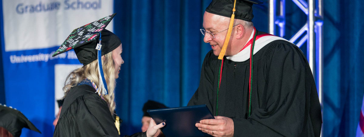 Dean Mike Decelle hands student diploma on stage