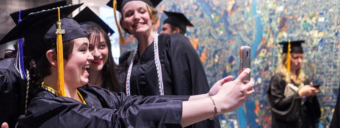 "UNH Manchester students taking a ""selfie'' at the 2015 commencement ceremony"
